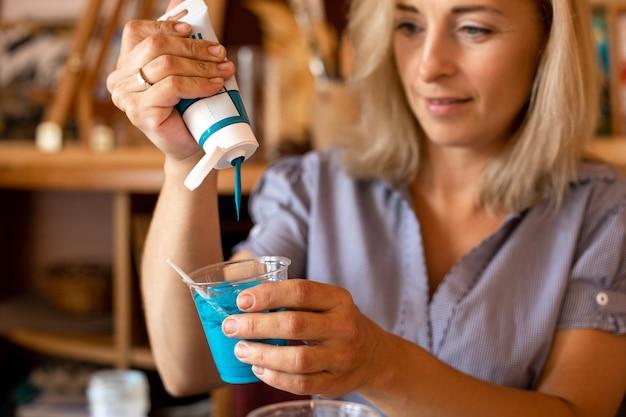Atraente artista feminina segura o copo de tinta nas mãos e espreme a tinta turquesa do tubo. trabalho em oficina criativa. pinturas de interiores. design e inspiração. trabalhe em casa.