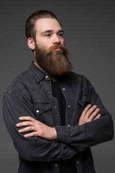 Atraente barba longa homem mãos cruzadas isolado fundo cinza
