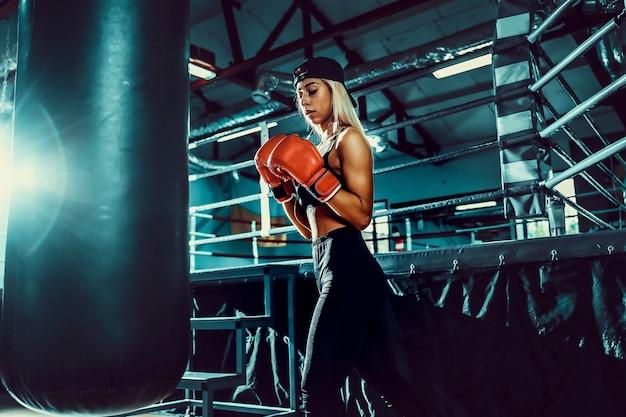 Atraente boxeadora de treino ao acertar um saco de boxe