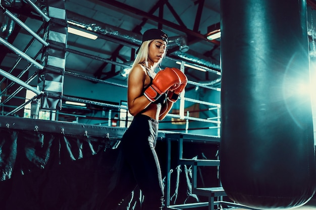 Atraente boxer feminina treino ao bater no saco de boxe