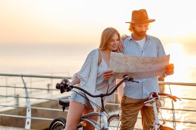 Atraente casal de amigos feliz viajando no verão em bicicletas, homem e mulher com cabelo loiro boho hipster estilo moda se divertindo juntos