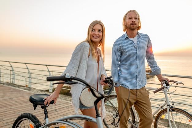 Atraente casal de amigos felizes viajando no verão em bicicletas, homem e mulher com cabelo loiro boho hipster estilo moda se divertindo juntos, caminhando à beira-mar nas férias