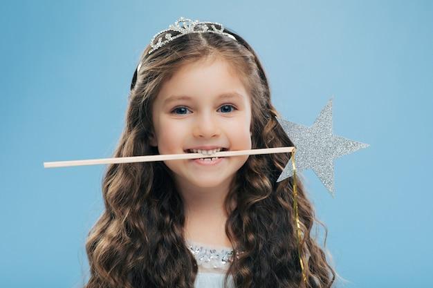 Atraente criança pequena sorridente detém varinha mágica na boca