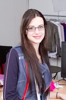 Atraente designer de moda feminina está trabalhando em sua oficina elegante showroom