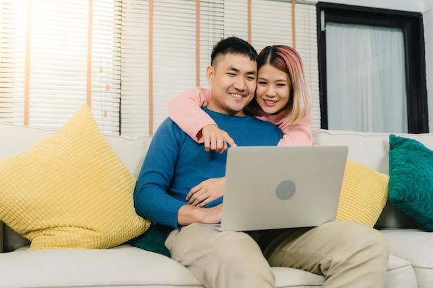 Atraente, doce asiático, par, usando computador, ou, laptop, enquanto, mentindo, sofá, quando, relaxe
