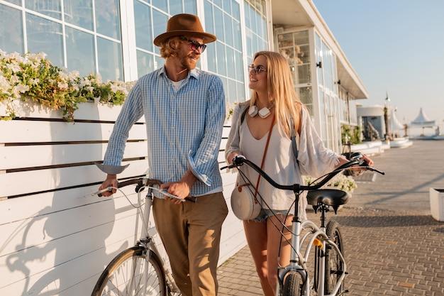 Atraente e feliz casal de amigos viajando no verão de bicicleta, homem e mulher com cabelos loiros