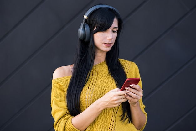 Atraente e linda garota morena caucasiana em fones de ouvido, ouvindo música em fones de ouvido e usando um smartphone sobre um fundo preto.