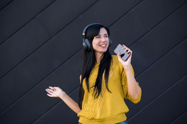 Atraente e linda garota morena caucasiana em fones de ouvido, ouvindo música em um suéter amarelo, segurando um smartphone, cantando e dançando sobre um fundo preto.