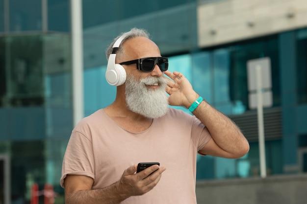 Atraente e sorridente barbudo velho sênior com cabelo branco, curtindo música do telefone inteligente ao ar livre usando fones de ouvido brancos.