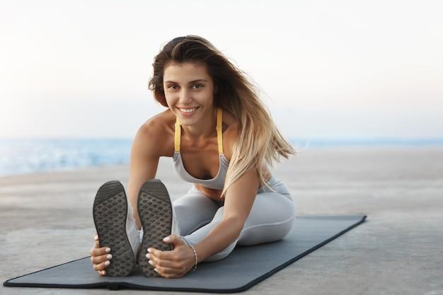 Atraente e sorridente instrutora de fitness mostrando exercício de treinamento esticando as pernas antes da sessão de treino