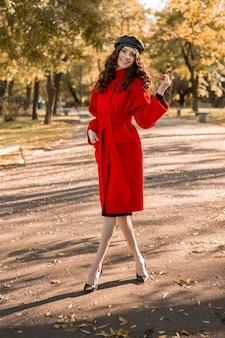 Atraente elegante e sorridente mulher magra com cabelo encaracolado caminhando no parque vestida com um casaco vermelho quente na moda do outono, estilo de rua, usando boina