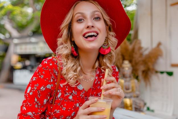 Atraente elegante loira sorridente com chapéu vermelho palha e blusa roupa da moda de verão bebendo suco de coquetel de frutas naturais