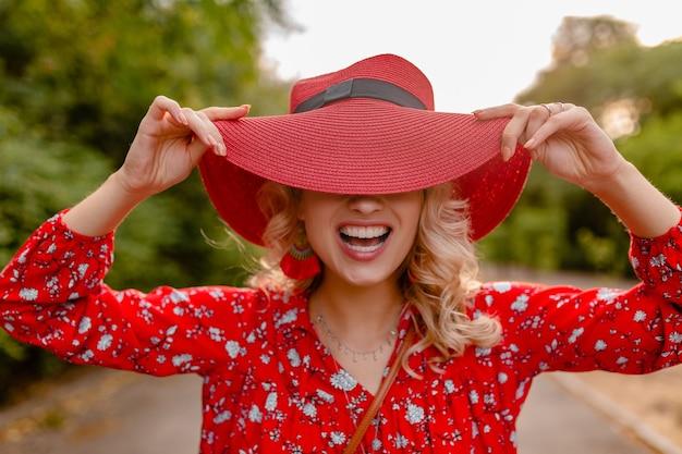Atraente elegante loira sorridente com chapéu vermelho palha e blusa roupa da moda de verão engraçado