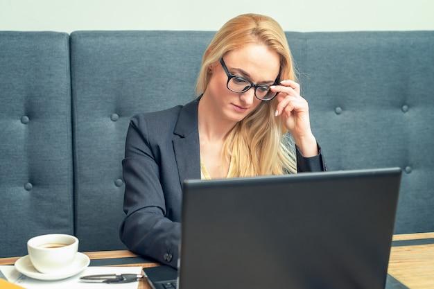 Atraente empresária madura em copos está trabalhando no laptop no escritório.