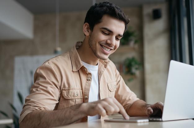 Atraente empresário asiático usando laptop e smartphone, trabalhando iniciar projeto no escritório