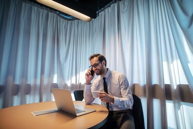 Atraente empresário bem sucedido ambicioso caucasiano de camisa e gravata e com óculos, tendo uma chamada de negócios, olhando para o laptop e segurando a xícara com café enquanto está sentado em seu escritório.
