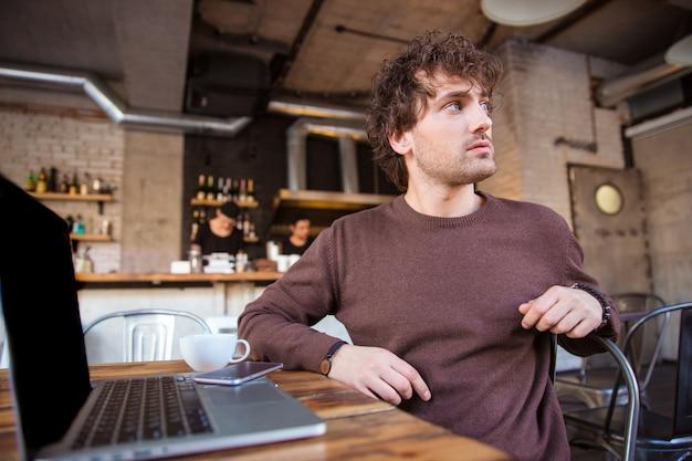 Atraente encaracolado pensativo concentrado bonito homem jovem em uma camiseta marrom sentado e olhando para longe do laptop