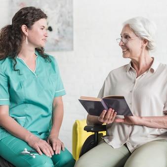 Atraente, enfermeira, olhar, sênior, mulher, paciente, sentando, ligado, cadeira roda, com, livro