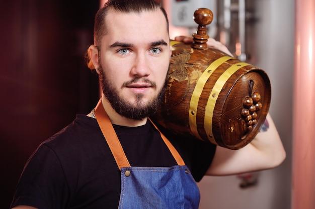 Atraente enólogo tem um barril de madeira de vinho