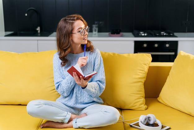Atraente escritor feminino em copos escreve seus registros pessoais em notebook enquanto está sentado no confortável sofá amarelo na elegante cozinha moderna.