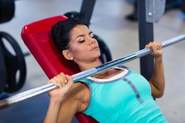 Atraente esportes mulher treino com barra no banco no ginásio de fitness