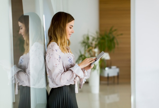 Atraente, executiva, usando, um, tablete digital, enquanto, ficar, em, escritório