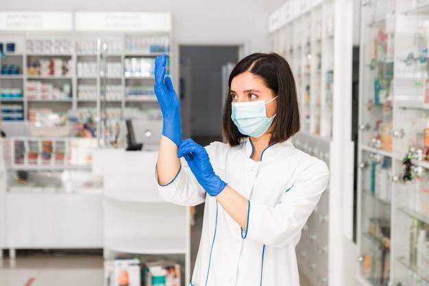 Atraente farmacêutica séria em farmácia com máscara no rosto calçando luvas azuis chegando a