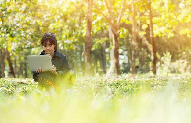 Atraente feliz asian young girl desfrutar de pesquisa, social com laptop para preparar final