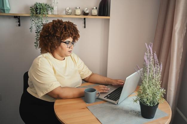 Atraente feliz elegante plus size estudante negra afro-americana de óculos estudando online