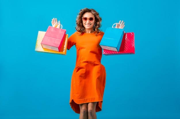 Atraente feliz emocional sorridente mulher viciada em compras em um vestido laranja superdimensionado segurando sacolas de compras no fundo azul do estúdio isolado