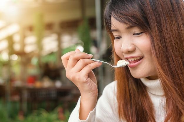 Atraente, feliz, fofa, jovem, asiática, mulher, sentando, comer, sobremesa, ao ar livre, café