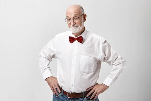 Atraente feliz idoso caucasiano homem de bom humor posando isolado no estúdio