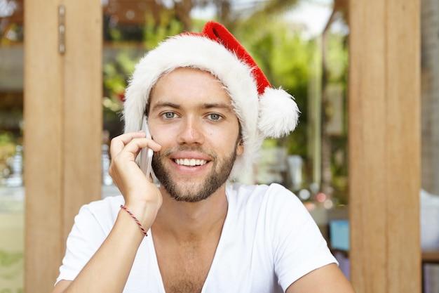 Atraente feliz jovem homem branco vestido com camiseta branca e chapéu de papai noel vermelho falando no smartphone