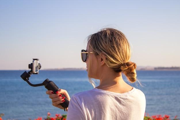 Atraente feminino grava vídeo com moderno 3d gimbal estabilizado smartphone da câmera