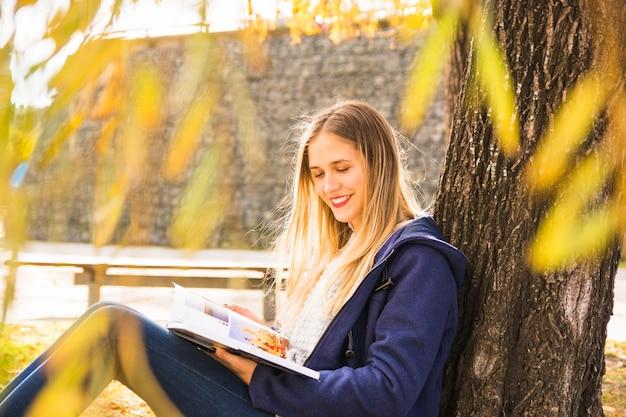 Atraente feminino lendo livro sob a coroa de árvore de outono