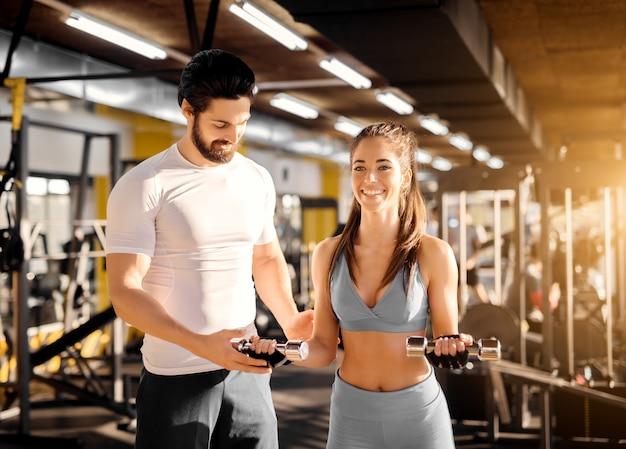 Atraente forte treinador muscular mostrando exercícios de bíceps com pequenos halteres para uma adorável garota sorridente no ginásio.