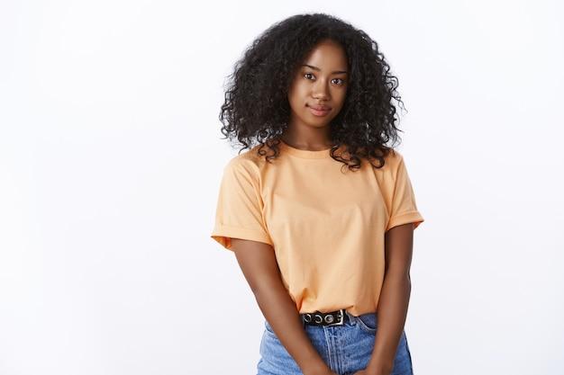 Atraente garota afro-americana estudante universitária com penteado encaracolado vestindo camiseta laranja da moda posando em uma linda parede branca, sorrindo, olhando a câmera despreocupada alegre, expressando positividade