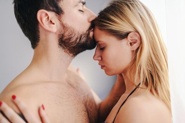 Atraente homem barbudo seminu com tatuagem ao lado da janela no quarto e beijando sua amada namorada na testa