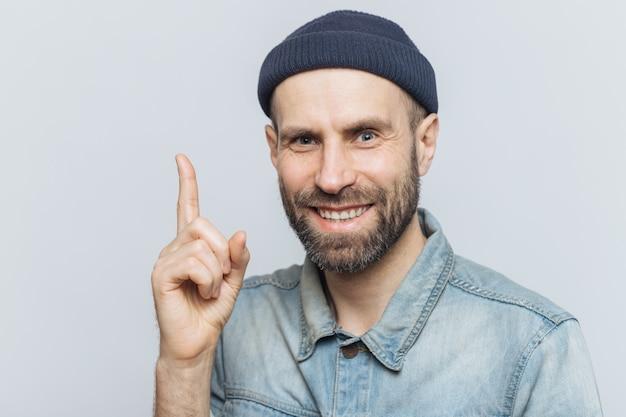 Atraente homem de meia idade levanta o dedo dianteiro, como tem uma boa idéia em mente, usa roupas da moda