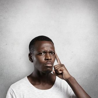 Atraente homem de pele escura vestindo camiseta branca, segurando o dedo na têmpora, tentando se lembrar de algo importante, franzindo a testa, parecendo concentrado e focado.