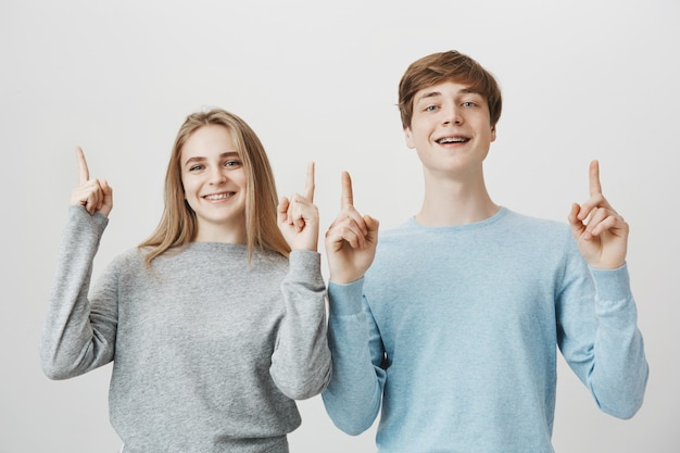 Atraente homem e mulher com aparelho, sorrindo e apontando os dedos para cima
