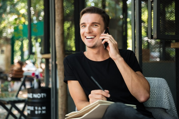 Atraente homem rindo falando no celular enquanto está sentado