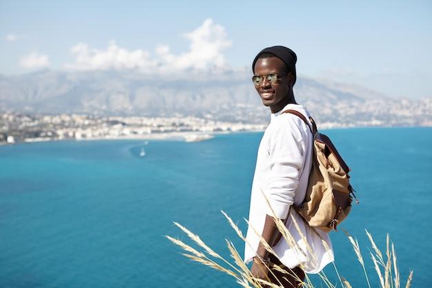 Atraente jovem alpinista afro-americana carregando mochila pequena, contemplando a vista incrível do azul do oceano, montanhas e cidade abaixo relaxante no topo da rocha após escalada esgotável em dia ensolarado