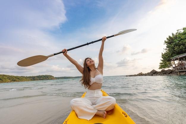 Atraente jovem asiática caiaque desfrutar com férias de verão na praia, sentindo-se tão feliz e alegre, viajar na praia tropical na tailândia, férias e relaxamento conceito