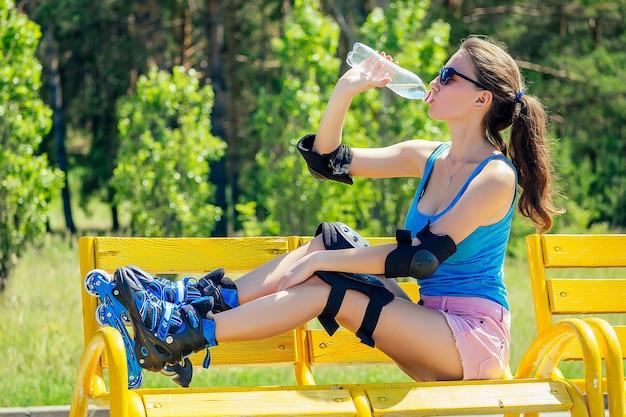 Atraente jovem atlética magro morena garota sexy em shorts rosa curtos e top azul com cotoveleiras de proteção e joelheiras patins é beber água de uma garrafa em um banco no parque de verão