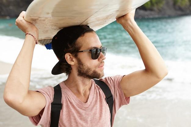 Atraente jovem barbudo vestindo óculos carregando bodyboard na cabeça e olhando para o oceano