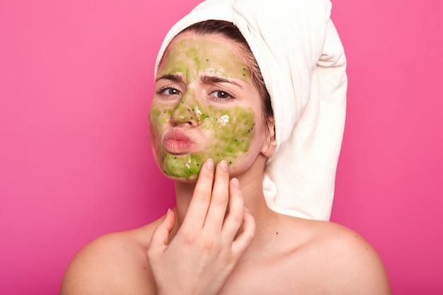 Atraente jovem beleza emocional tem máscara verde no rosto, dia para ter procedimentos de spa, sobressai os lábios, tem expressão facial desagradável. poses de modelo magnético isoladas em rosa.