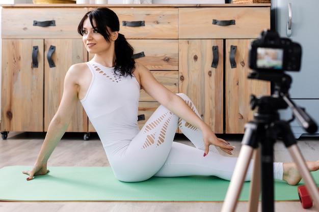 Atraente jovem blogueiro sorrindo e esticando enquanto está sentado no tapete e fazendo um vídeo para o blog dela