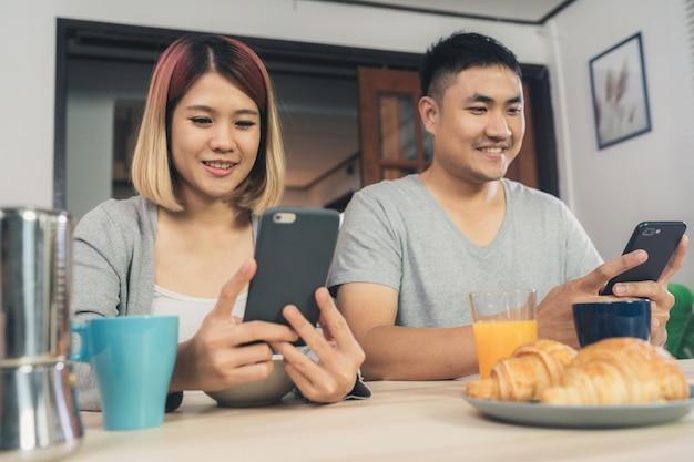 Atraente jovem casal asiático distraído na mesa com jornal e telefone celular