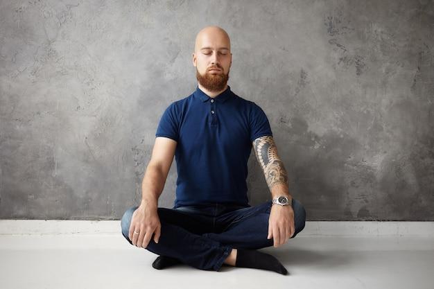 Atraente jovem caucasiano com espessa barba ruiva e braço tatuado relaxando depois do trabalho, sentado no chão, fechando os olhos e cruzando as pernas, deixando de lado todos os pensamentos negativos, tendo o olhar focado